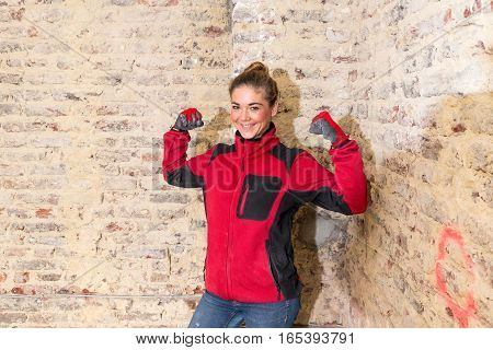 Dynamic Craftswoman In Front Of Brick Wall In Bare Brickwork