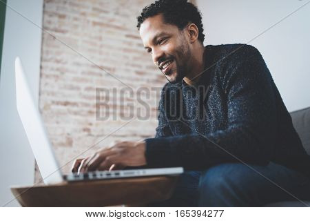 Cheerful African man using computer and smiling while sitting on the sofa. Concept of young business people working at home. Blurred background