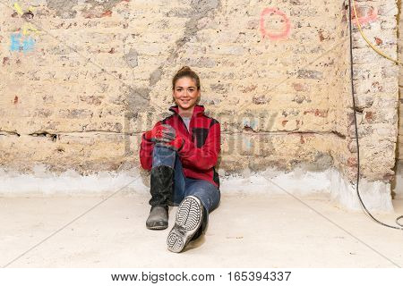 Ambitious Craftswoman Sitting On Floor In Front Of Brick Wall In Bare Brickwork