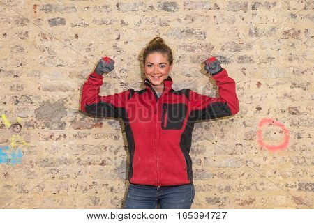 Dedicated Craftswoman In Front Of Brick Wall In Bare Brickwork