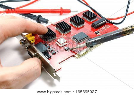Replacement of electronic component on the DVR motherboard with a soldering iron on a white background