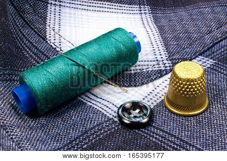 Green thread on a plastic spool with thimble and a button on the background of the shirt