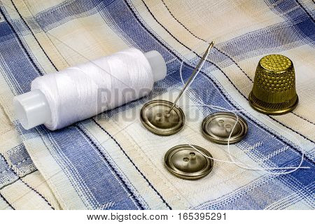 White thread on a plastic spool with needle thimble and buttons