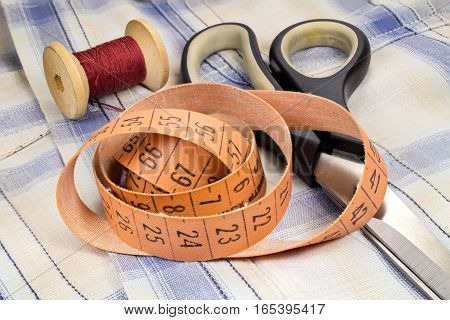 The tailor's tape measure a wooden spool of thread and dressmakers scissors on fabric background