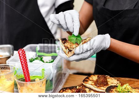 Female street vendor hands making taco outdoors. Mexican cuisine snacks, cooking fast food for commercial kitchen.