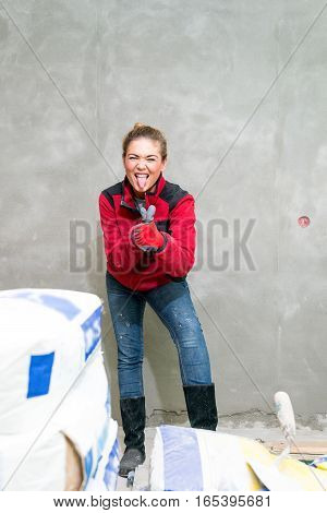 Craftswoman With Thumbs Up In Between Cement Bags In Front Of Rendered Wall