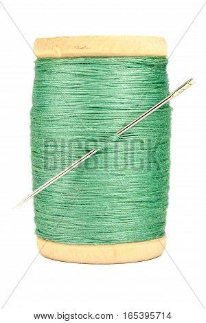 Old wooden spool of thread and needle on white background
