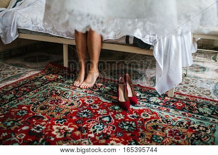 Bride getting ready to wear wedding shoes Red