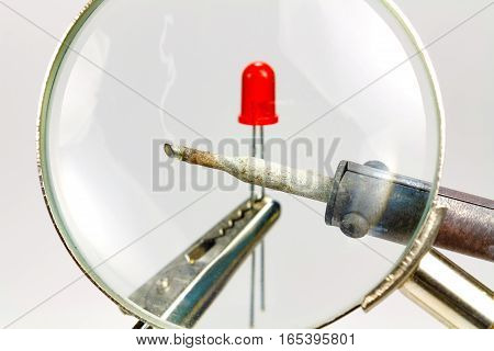 Soldering iron and red LED diode through a magnifying glass