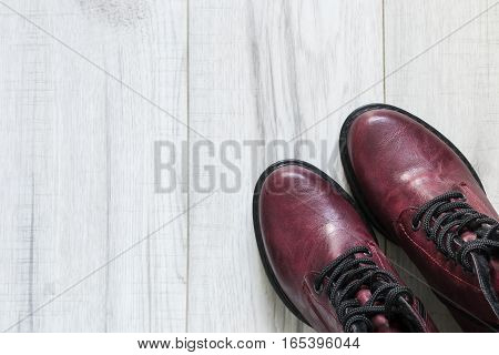Pair of maroon laced boots on wooden floor closeup