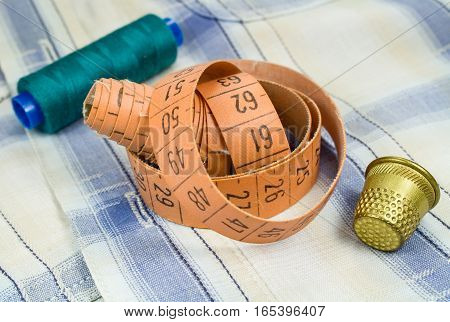 The tailor's tape measure with a thimble and a spool of thread on a fabric background