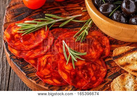 Spanish traditional chorizo sausage with fresh herbs olives tomatoes on a wooden board.