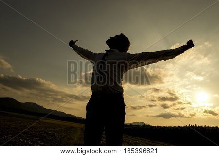Low angle three quarter body view of silhouetted person with spread arms in countryside sunset freedom concept.