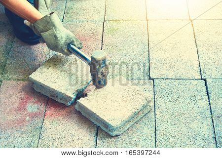 Person holding hammer and smash to the brick vintage style and soft focus