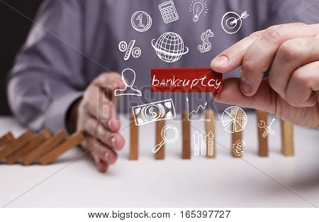 Business, Technology, Internet And Network Concept. Young Businessman Shows The Word: Bankruptcy