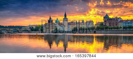 Prague. Panoramic image of Prague riverside and Charles Bridge, with reflection of the city in Vltava River.