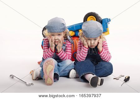 two cute little twin girls repairing car