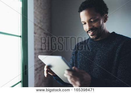 Selective focus.Smiling bearded African man reading news digital tablet while standing near the window in his modern apartment.Concept of young business people working at home.Blurred background