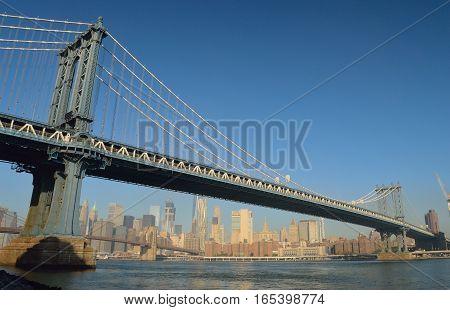 Manhattan Bridge against a clear blue sky.