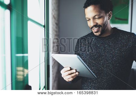 Selective focus. Smiling bearded African man reading book on digital tablet while standing near the window in his modern apartment. Concept of young business people working at home. Blurred background.
