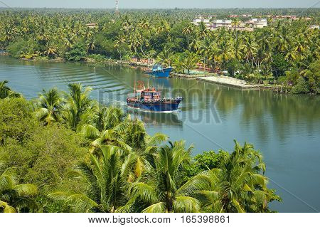 tropical river with trawlers in Southeast Asia. Palm trees coming in from ocean ships
