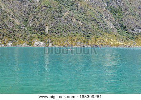 Minimal style photo with people at small boat sailing an inmense lake at Quilotoa crater Latacunga Ecuador