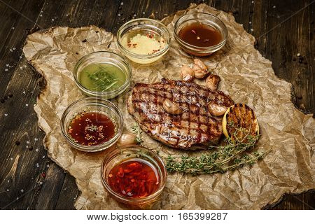 grilled steak with different sauces, on parchment. vertical top view.