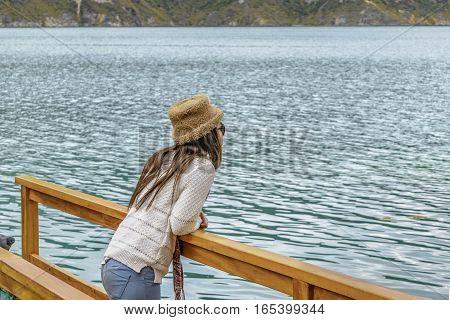 QUILOTOA, ECUADOR, FEBRAURY - 2016 - Young woman contemplating the view at Quilotoa lake Latacunga Ecuador