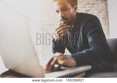 Pensive young African businessman using laptop while sitting on sofa at his modern coworking place. Concept of business people. Blurred background, color filter, flare effect.