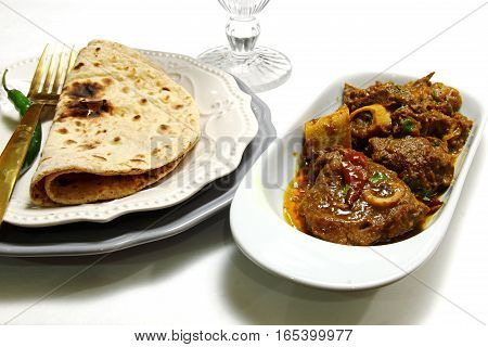 A bowl of mutton curry or Rogan josh and a plate of Chapati on white background