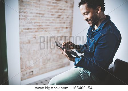 Musing bearded African American freelancer touching display of digital tablet while working in new project at home. Black businessman looking for information on Internet. Blurred, color filter