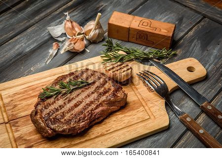 Pork steak on wooden Board with herbs, garlic and black pepper.
