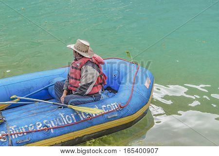QUILOTOA, ECUADOR, FEBRAURY - 2016 - Adult worker man sitting at raft boat at Quilotoa lake Latacunga Ecuador
