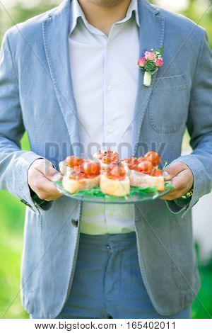 Handsome Groom In A Wedding Suit With Boutonniere And Sandwiches In Hands