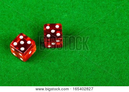Two gambling dice on a card table showing double 5