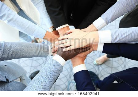 Group of business people joining hands in office