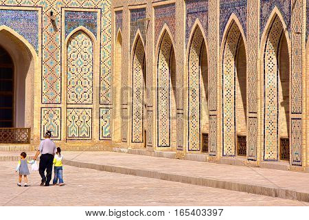 BUKHARA, UZBEKISTAN - MAY 9, 2011: An Uzbek man with his two children walking in the courtyard of the Poy Kalon mosque