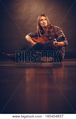 Hobby music concept. Young boy with guitar. Man is sitting on the floor and playing the instrument.