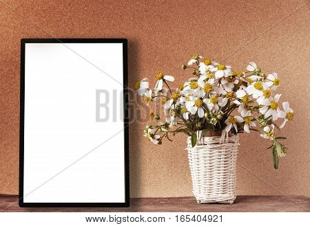 Blank white frame mockup with chamomile flowers in bamboo basket on wooden table on vintage tone. Poster product design styled mock-up.