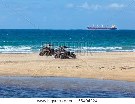 People ride ATV along the sea shore