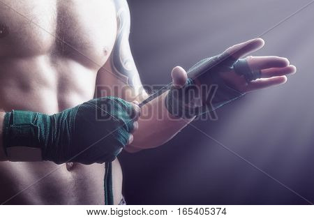 Close up of a boxer putting on straps preparing for combat