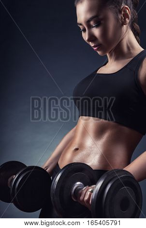 Fitness young woman with heavy weights on a dark background