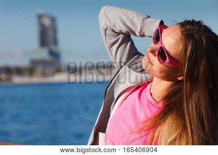 Sport workout fashion concept. Woman wearing sunglasses and tracksuit resting relaxing after doing sports outdoors near sea