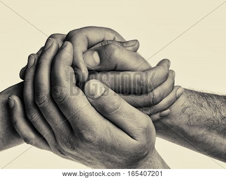 Men's hands hold the female palm on isolated toned background. That could mean help guardianship protection love care etc.