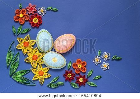Colorful easter composition with eggs and flowers in the technique of quilling on a blue background. Homemade application on paper. DIY Easter concept. Top view