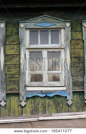 beautiful vintage traditional Russian wooden windows with decoration on green wall