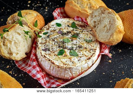 Homemade Baked Camembert cheese with thyme and fresh bread.
