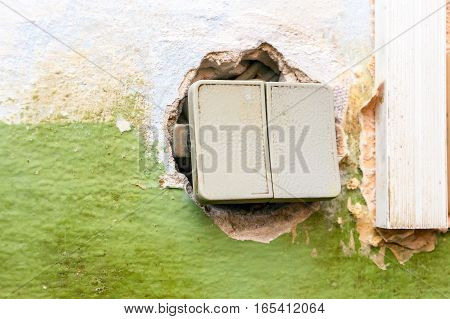A broken light switch with exposed wires on a dirty old wall