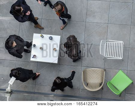 Bucharest Romania March 18 2016: People are smoking and drinking coffee in an outdoor smoking area of an office building in Bucharest.