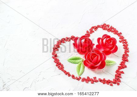 Sweet decoration: wafer roses and sugar hearts on a white textured background. The mood of tenderness and love. Symbols of Valentines Day